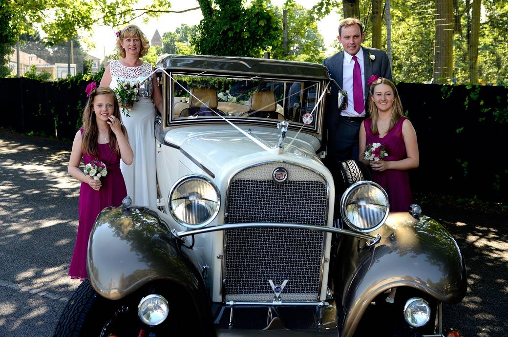 Bride Groom and Bridesmaids pose on the running boards of a Brenchley Landaulette vintage car taken at Surrey wedding venue Glenmore House in Surbiton