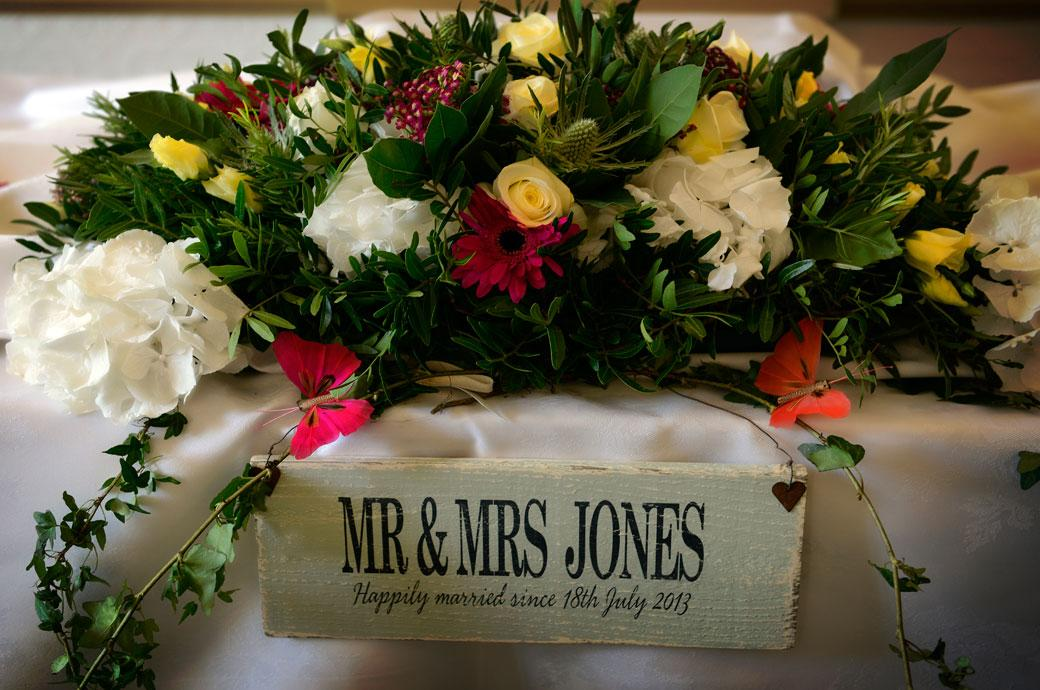 Beautiful  table flower bouquet and newly-weds sign in this wedding photograph captured by Surrey Lane wedding photography at Glenmore House