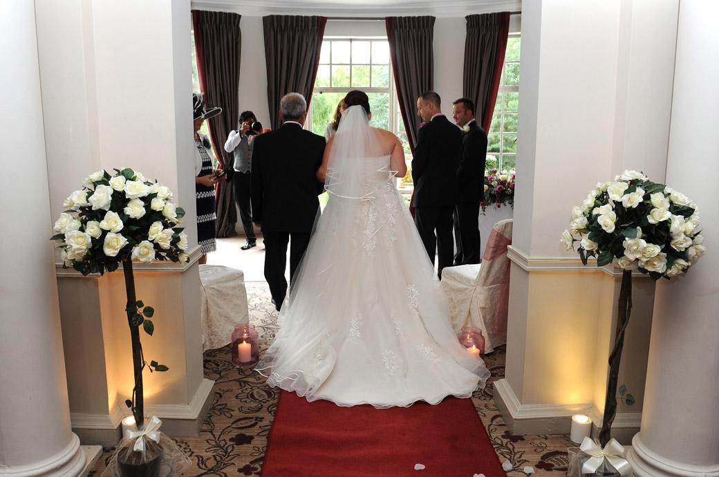 A view from the back of the red carpet as the Bride on her father's arm approaches the Groom at Surrey wedding venue Gorse Hill for the start of their marriage ceremony