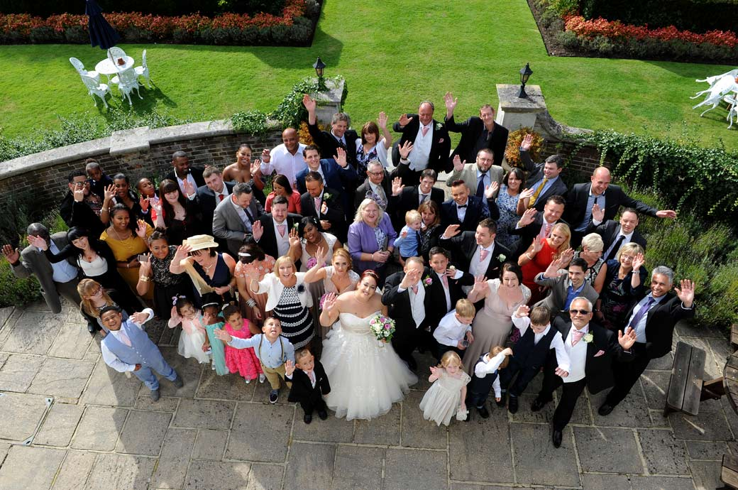 Everyone on the patio at the wedding waving at the Surrey Lane wedding photographer at Gorse Hill Woking  captured from an upstairs window