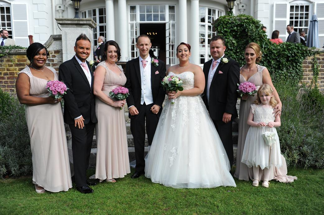 Newlyweds at Surrey wedding venue Gorse Hill in Woking standing with their Bridesmaids and Groomsmen in a wedding photograph out on the lawn on a sunny day