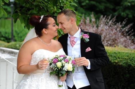 Smiling and happy groom and Bride touch noses together as they celebrate with champagne after getting married at Gorse Hill a popular and relaxed wedding venue in Woking Surrey