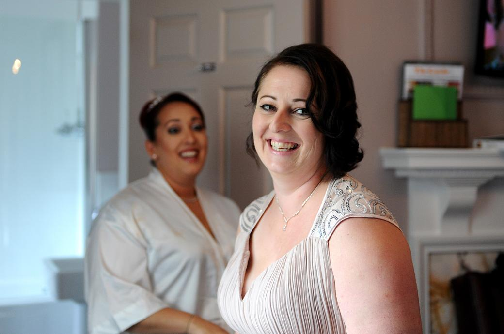 Smiling Bridesmaid sharing a joke with the happy bride at  Surrey wedding venue Gorse Hill as she gets ready in the bridal suite before the marriage ceremony