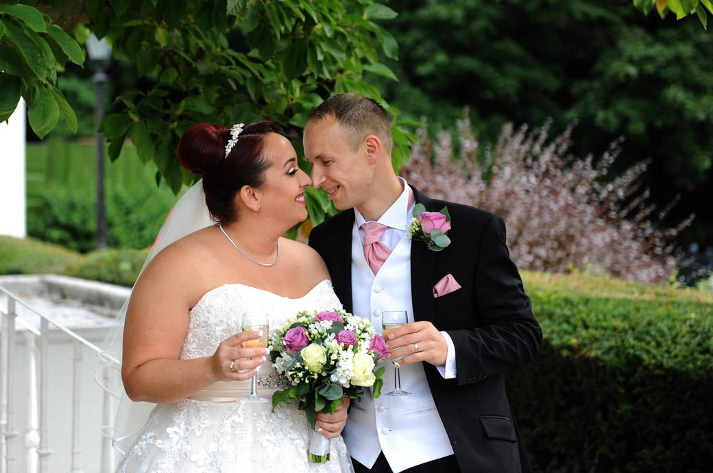 Lovely wedding picture of a Bride and groom getting intimate as they celebrate their recent marriage with champagne outside Surrey wedding venue Gorse Hill in Woking