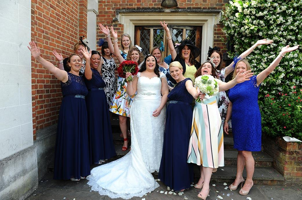 Happy relaxed wedding group photo of the Bride enjoying herself with her hen night ladies on the terrace steps at the wonderful Surrey wedding venue Great Fosters in Egham