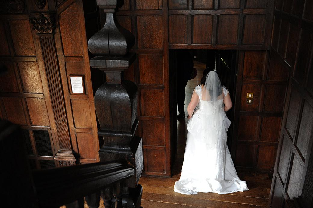 The Bride ready to enter the Great Hall having descended the  ancient oak staircase from the Tapestry Room now on route for The Orangery at Surrey wedding venue Great Fosters