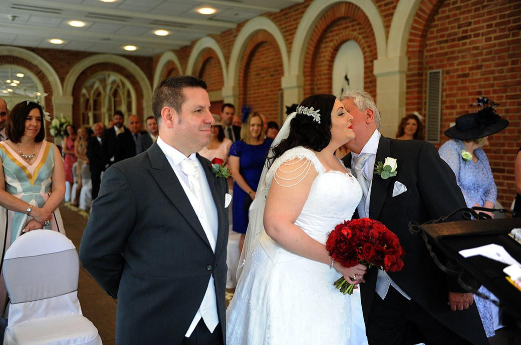Groom smiles as his Bride air kisses her father in this wedding photo taken as they stand before the marriage registrar at Surrey wedding venue Great Fosters in The Orangery
