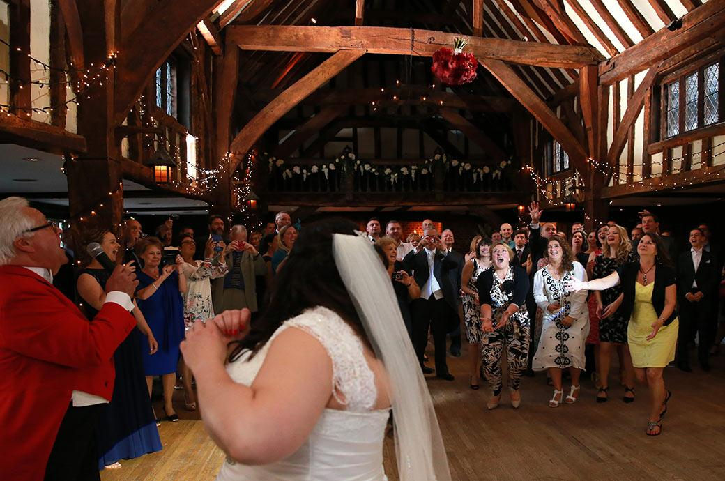 Surrey Lane wedding photographer in the Tithe Barn at the Great Fosters venue in Egham captures the bridal bouquet in mid flight heading towards the waiting ladies