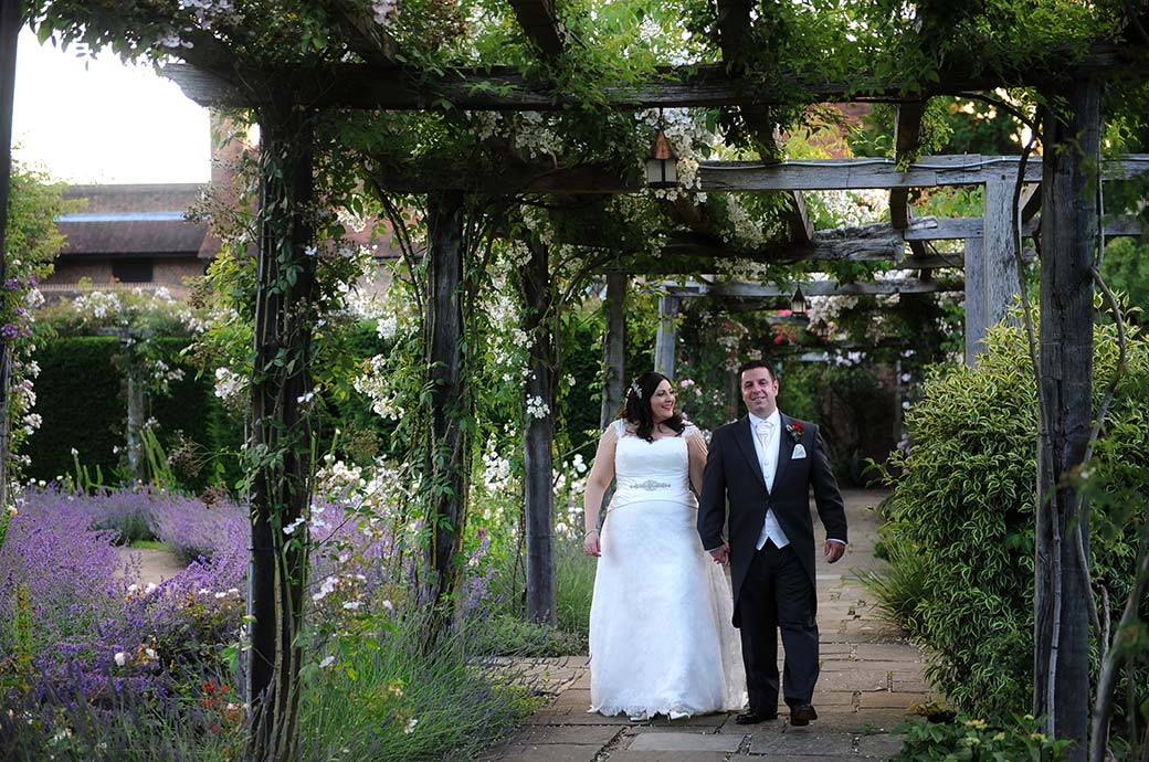 Romantic walk for the relaxed and content newlyweds as they take time out to explore the beautiful grounds of Great Fosters in Egham Surrey including the stunning rose garden