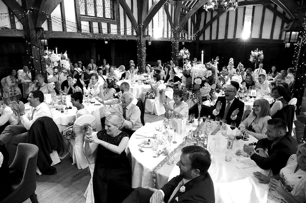 The wedding guests erupt into applause and laughter during the very funny best Men's wedding speeches captured at Surrey wedding venue Great Fosters in The Tithe Barn