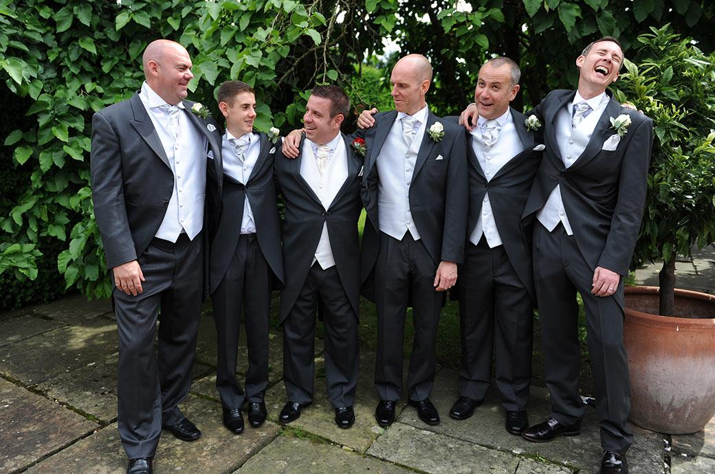 Smiles fun and laughter as the Groom along with his groomsmen enjoy getting together to pose for their Surrey Lane wedding photographer out on the terrace