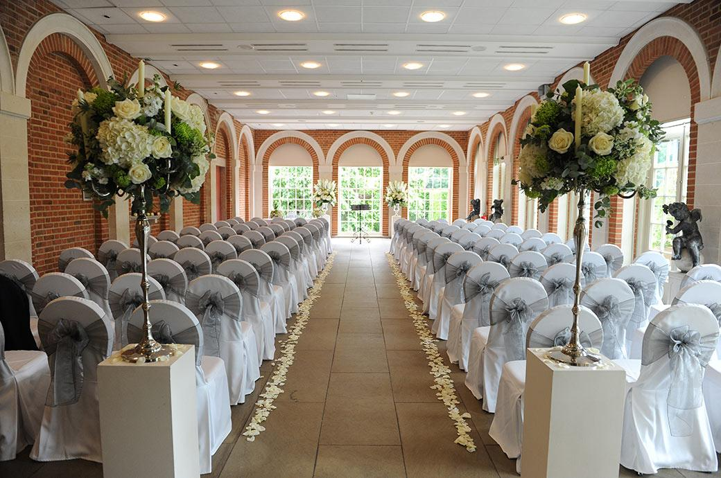 Looking down the impressive rose petal covered aisle fronted by beautiful flower displays and complete with statues is the Great Fosters Orangery in Egham Surrey