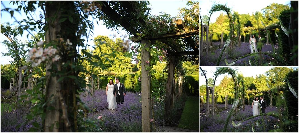Beautiful wedding photographs of the Bride and groom at Great Fosters in Surrey taking a romantic walk in the beautiful sunken rose garden passed the overflowing lavender