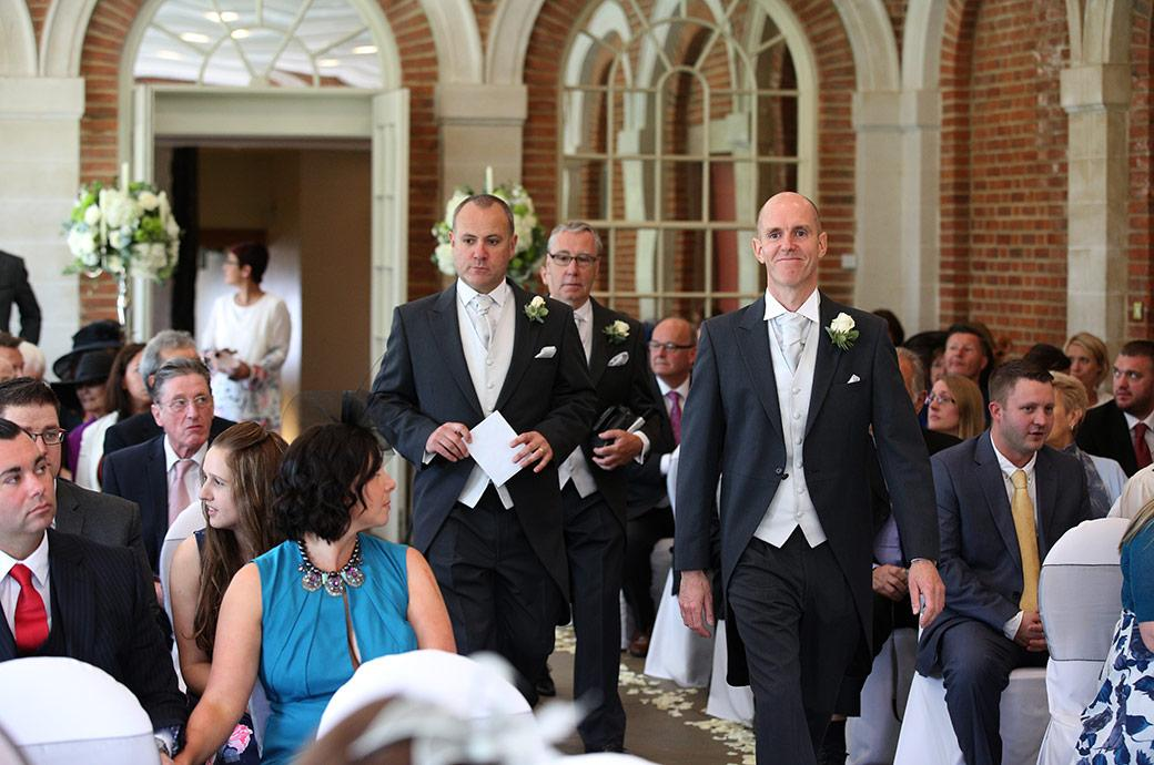 Groomsmen walking down the aisle of the bright and airy Orangery at the fabulous Surrey wedding venue Great Fosters Egham just before the arrival of the Bride