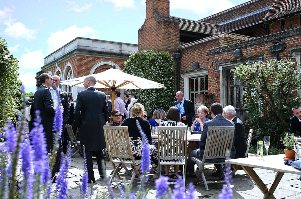 A wedding photo taken through the lavender of guests enjoying themselves in conversation on the terrace at the wonderful Great Fosters hotel in Egham Surrey