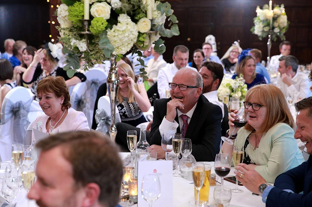 Lots of smiles and laughter captured by the Surrey Lane wedding photographers in the Tithe Barn at Great Fosters in Egham Surrey during the entertaining wedding speeches
