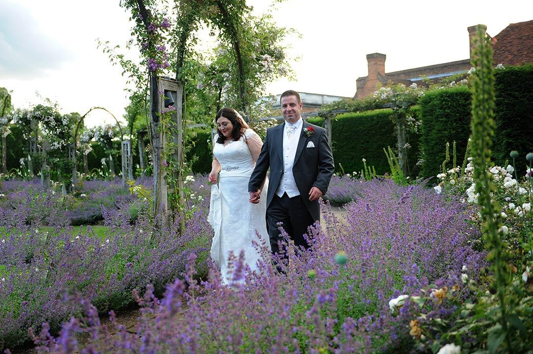 Smiling happy groom hand in hand with his smiling Bride at the stunning Surrey wedding venue Great Fosters in Egham as they walk in the sunken rose garden full of lavender