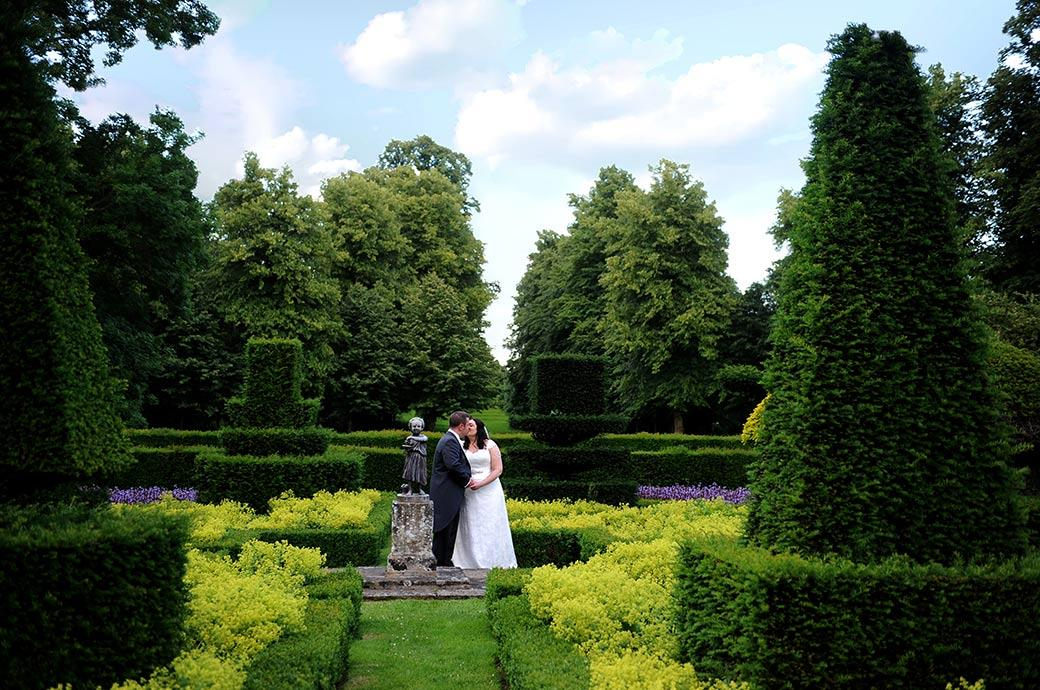 Bride and groom romantically kiss in this classic wedding photograph taken at the stunning Surrey wedding venue Great Fosters in the eye catching parterre garden