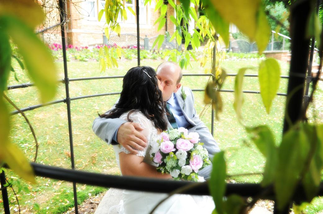 Romantic wedding picture taken through the leaves into the rose arbour of the newlyweds kissing at Guildford Register Office Artington House a popular Surrey wedding venue