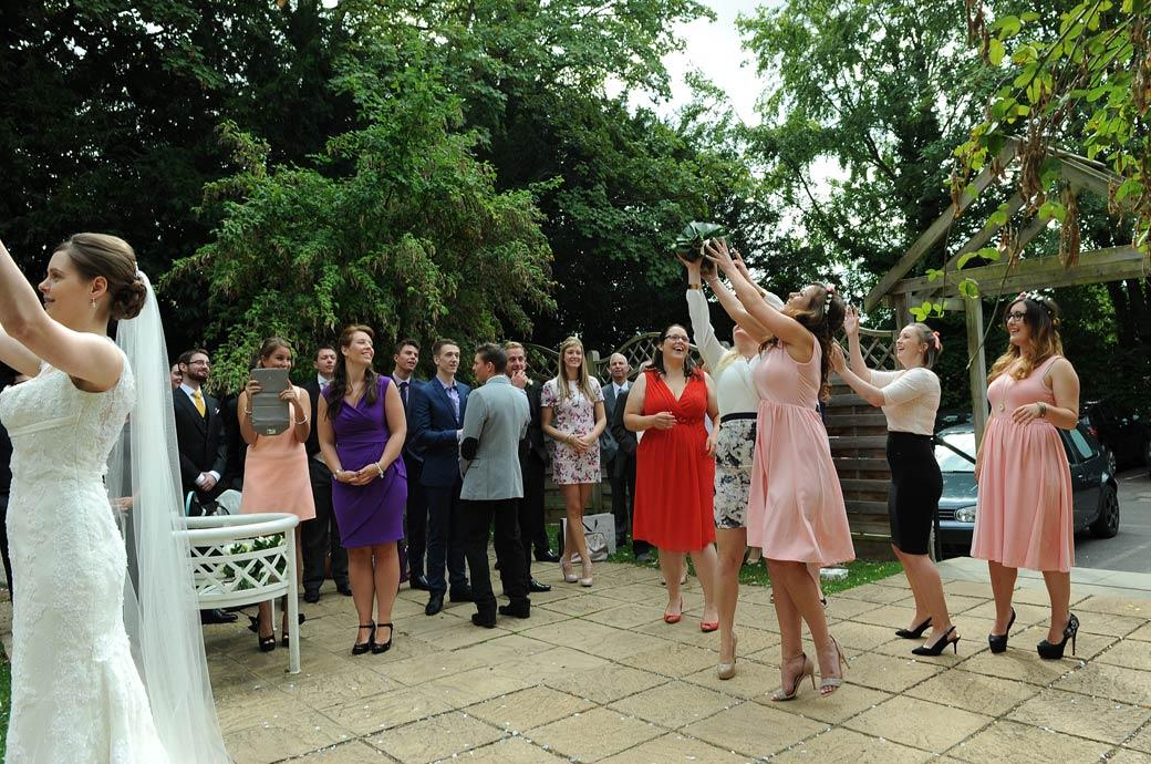 Ladies have fun catching the Bride's bouquet captured in this wedding photograph taken on the terrace of Surrey wedding venue Guildford Register Office