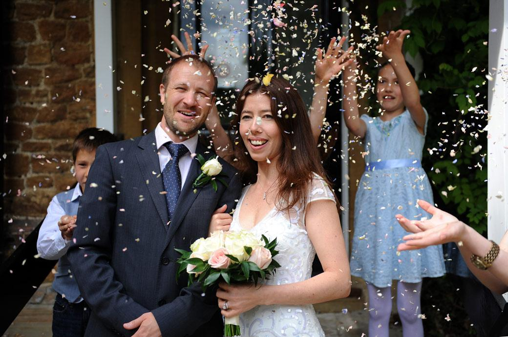 Happy newlywed couple standing on the steps of the  Artington House Guildford Register Office in Surrey as they are showered with wedding confetti