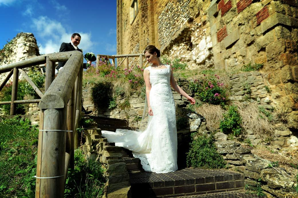 An elegant Bride descending steps in her beautiful dress from Guildford Castle in Surrey captured in this wedding photograph taken in Guildford Castle Gardens