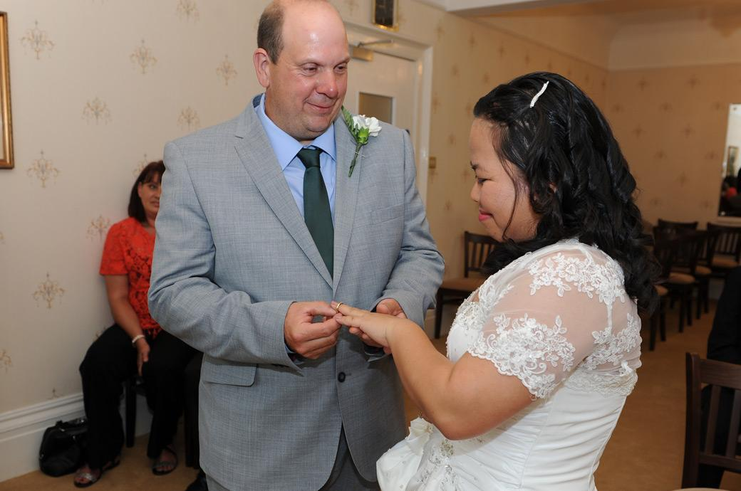 A proud Groom places the wedding ring on his excited Bride's finger in wedding photo from The Guildown Room in Artington House at Guildford Register Office in Surrey
