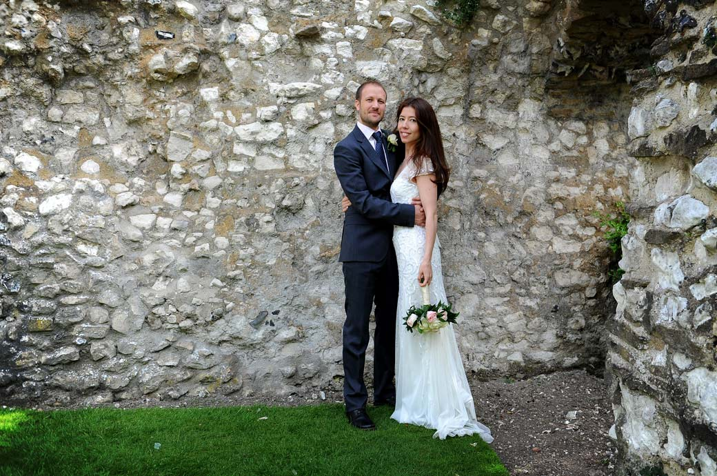 Handsome newlywed couple pictured standing in this wedding photograph taken by a Surrey Lane wedding photographer in the gardens by the ancient walls of Guildford Castle