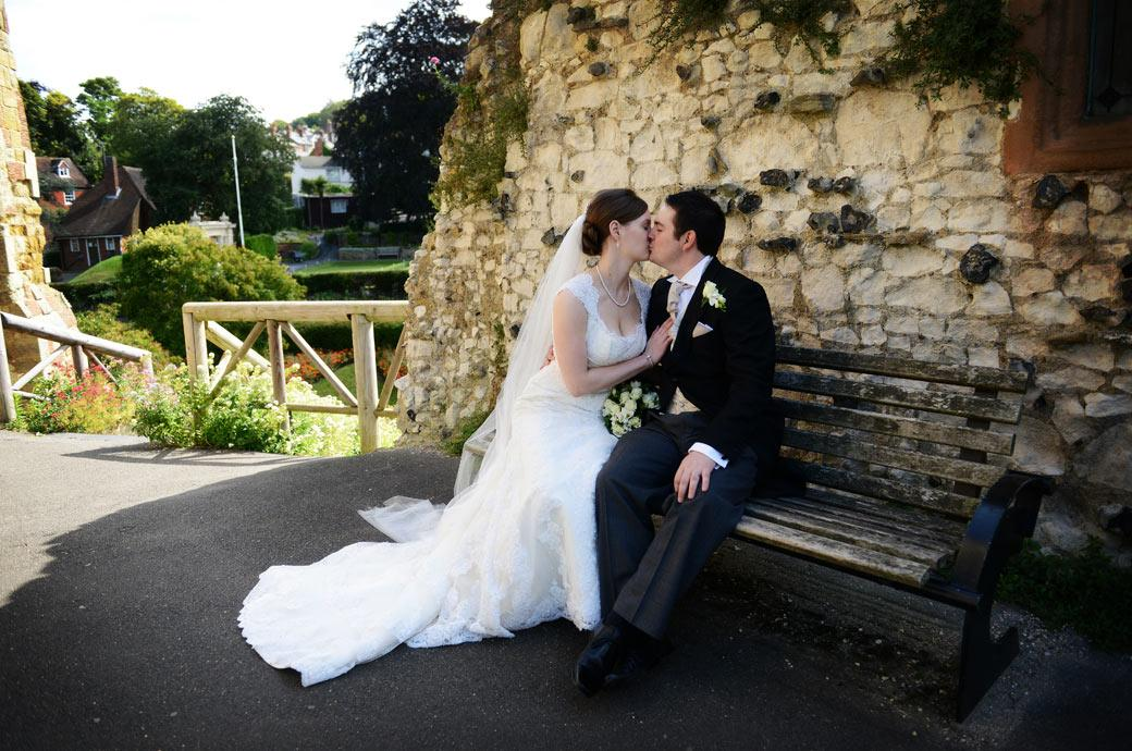 Beautiful romantic wedding photo of a newly-wed couple kissing on a bench in the beautiful Guildford Castle Gardens by Surrey Lane wedding photographers