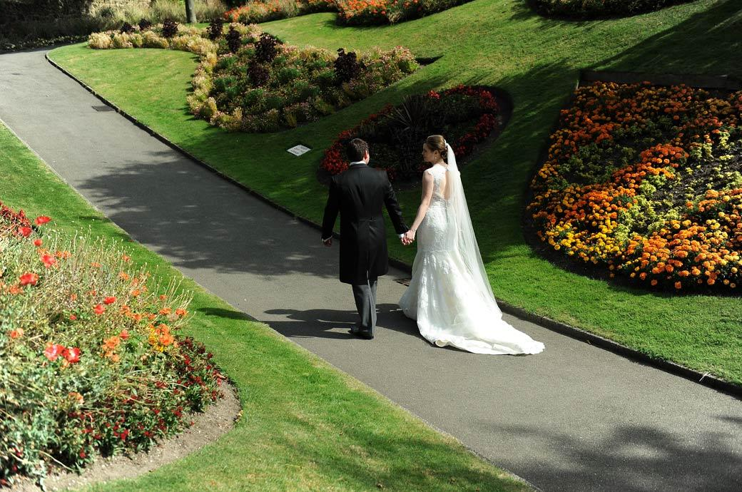 Newly-wed couple walking along the path hand in hand in this delightfully relaxed and romantic wedding picture in the Castle Gardens Guildford Surrey