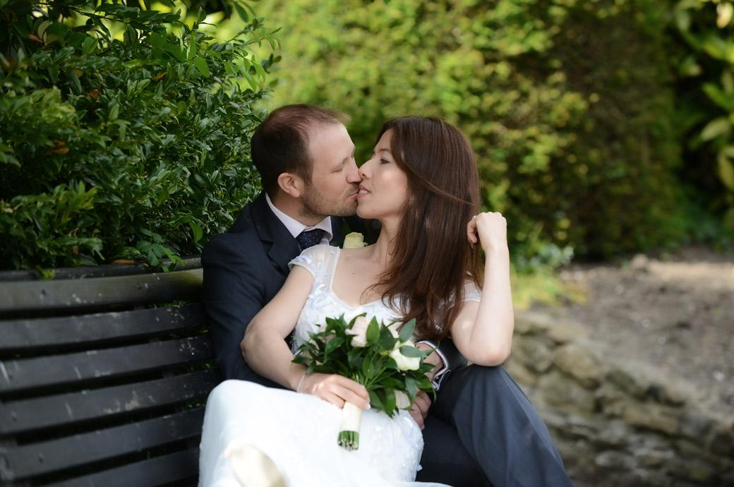 Gentle romantic moment for the newlywed couple as they sit on a park bench and kiss in Guildford Castle Gardens taken by Surrey Lane wedding photographers