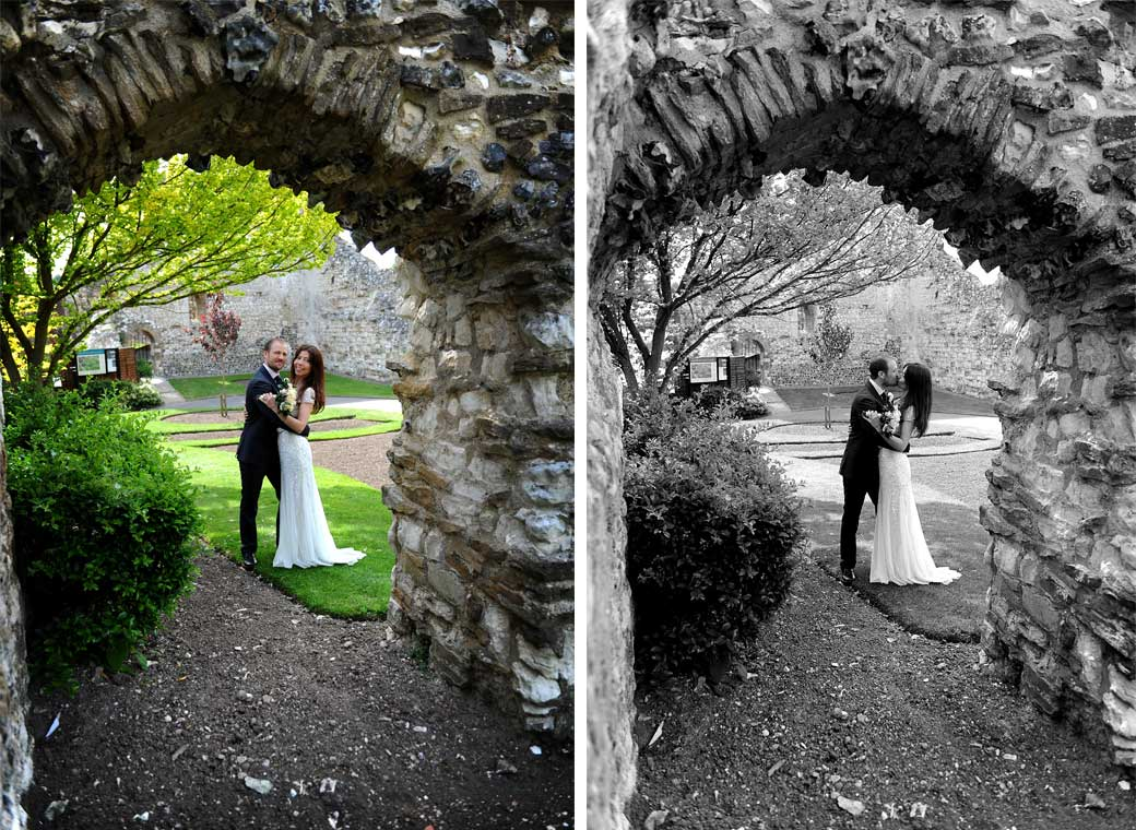 Romantic Bride and groom wedding pictures captured in the pretty Guildford Castle Gardens taken through flint arches in this popular Surrey tourist landmark