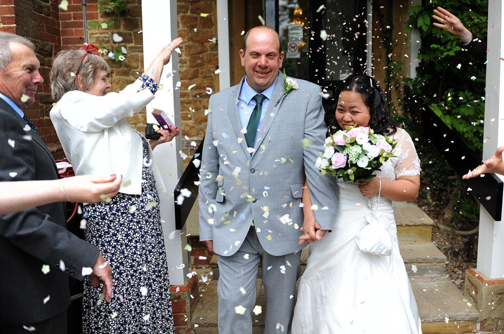 All smiles as the happy newlyweds walks down the path from Guildford Register Office in Artington House Surrey as their guests shower them with wedding confetti