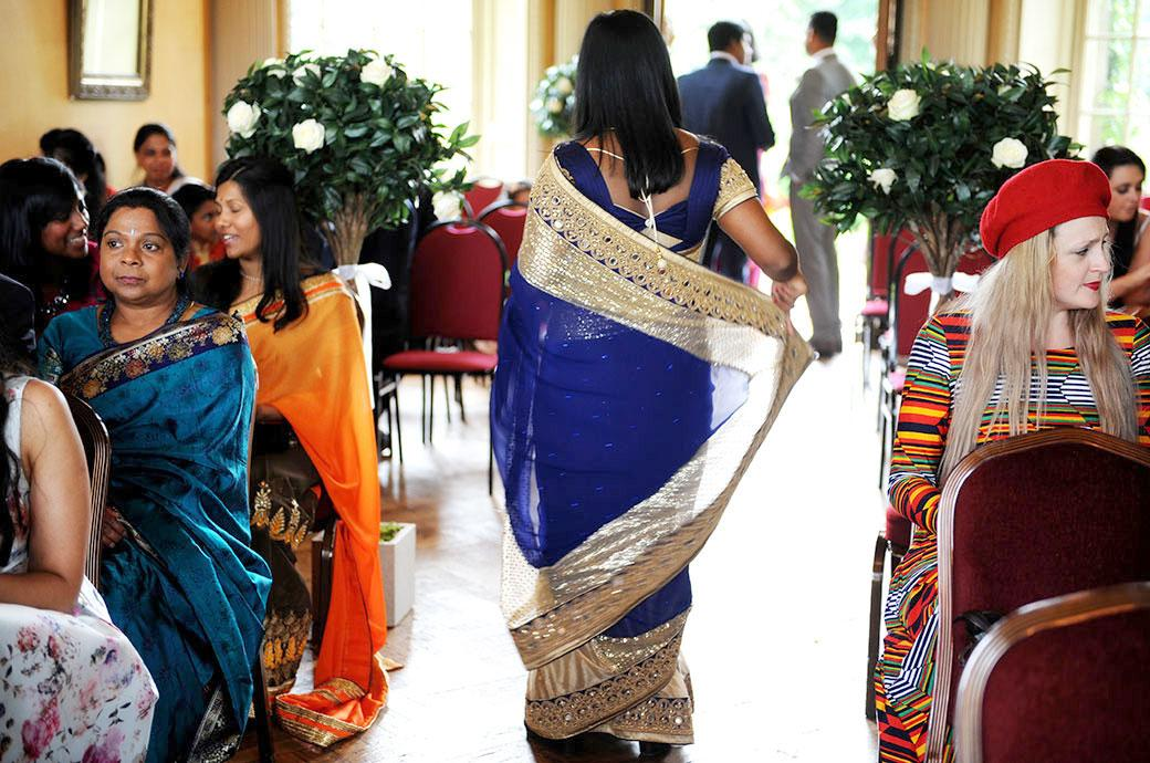 Wedding photograph of colourful ladies dresses and saris on show at Surrey wedding venue Hampton Court House down the aisle in the Main Hall