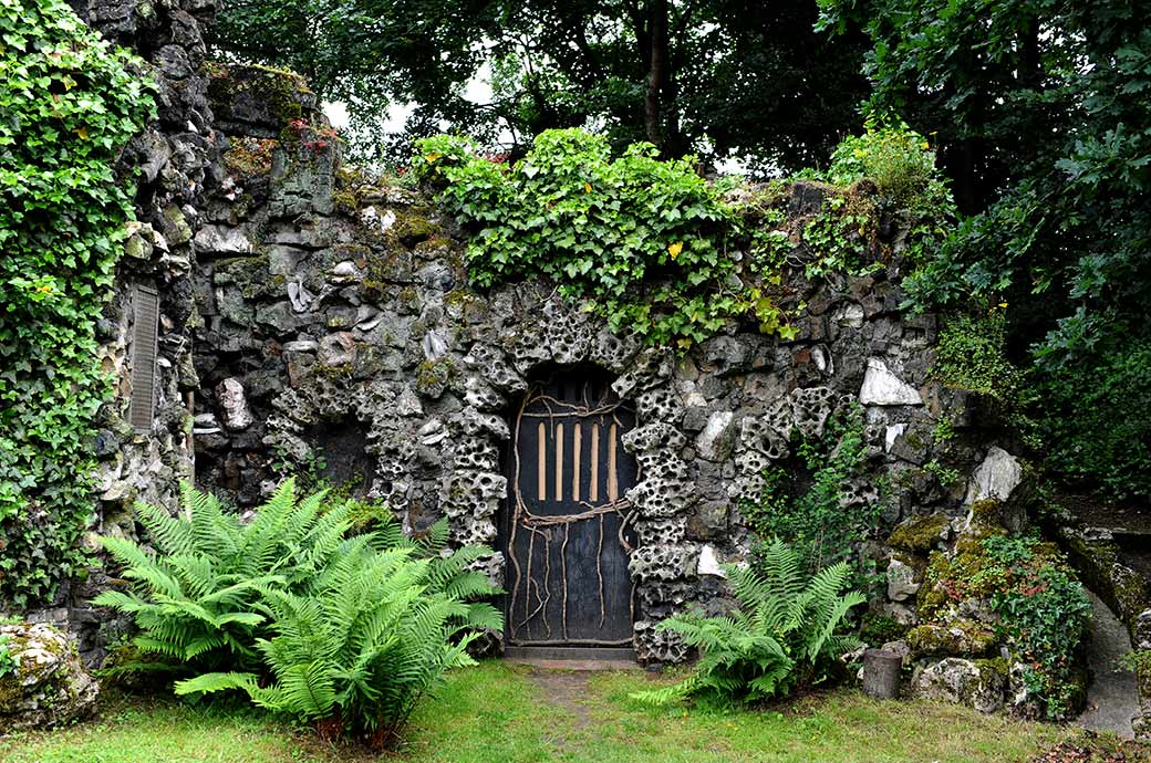 Picture of the front door taken at Hampton Court House in Surrey leading into the fascinating and mysterious looking vine covered shell grotto located beyond the lake