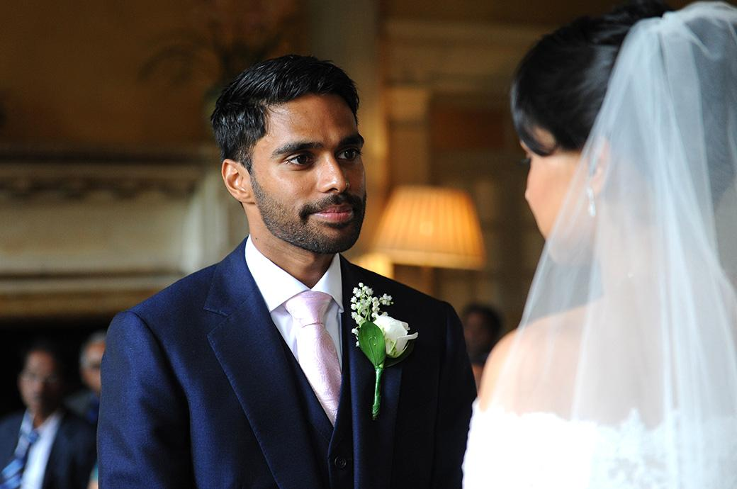 A loving Groom at Surrey wedding venue Hampton Court House looks into the eyes of his Bride as he says his vows during the marriage ceremony in the Main Hall