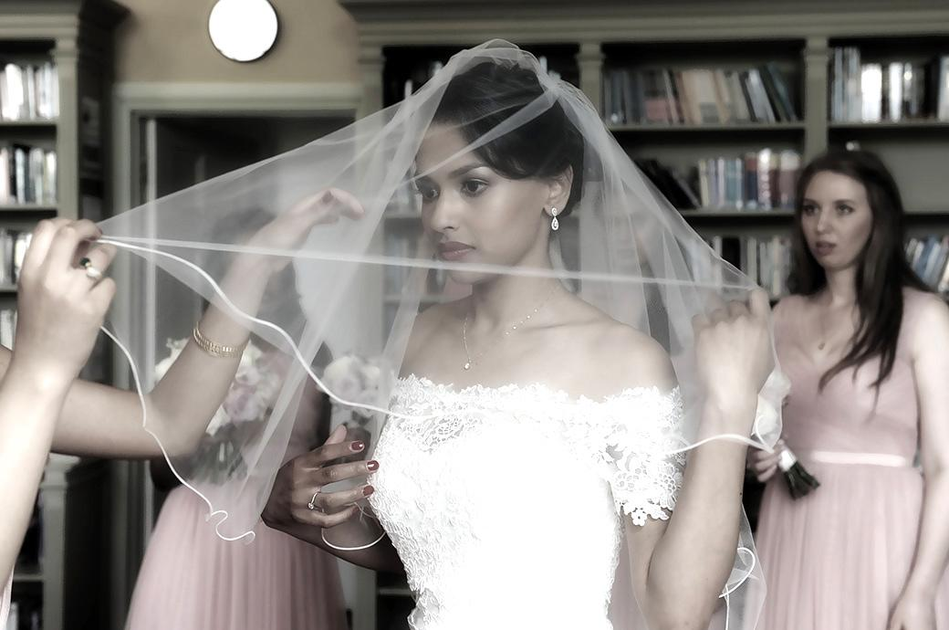 Beautiful Bride caught in the moment as she helped on with her wedding veil in an outer room at Surrey wedding venue Hampton Court House before entering the Main Hall