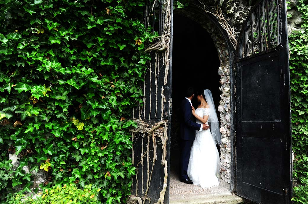 View past the ivy covered walls and doors of the shell grotto captured at Surrey wedding venue Hampton Court House of the  newlyweds holding each other in the doorway