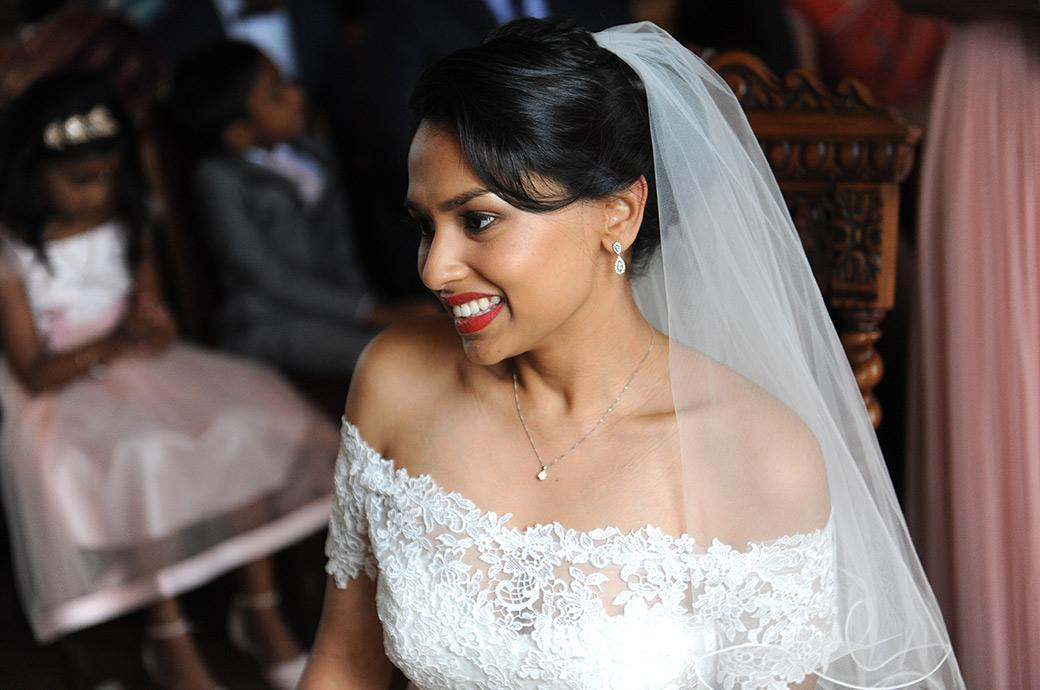 Lovely wedding picture of a happy smiling Bride after her marriage at Surrey wedding venue Hampton Court House close to the world famous Hampton Court Palace