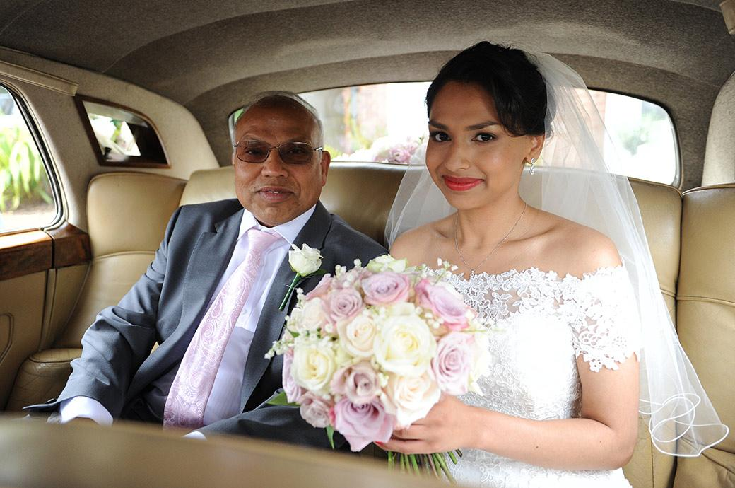 Lovely wedding photo of a smiling Bride with her father sitting in the Rolls Royce wedding car on their way to the Surrey wedding venue Hampton Court House