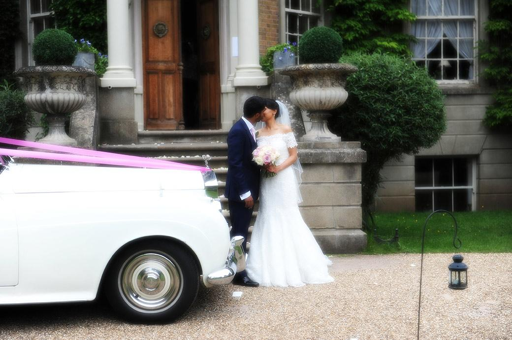 Romantic kiss by the newlyweds on the gravel drive of wedding venue Hampton Court House Surrey next to their white Rolls Royce with it's bright pink ribbon