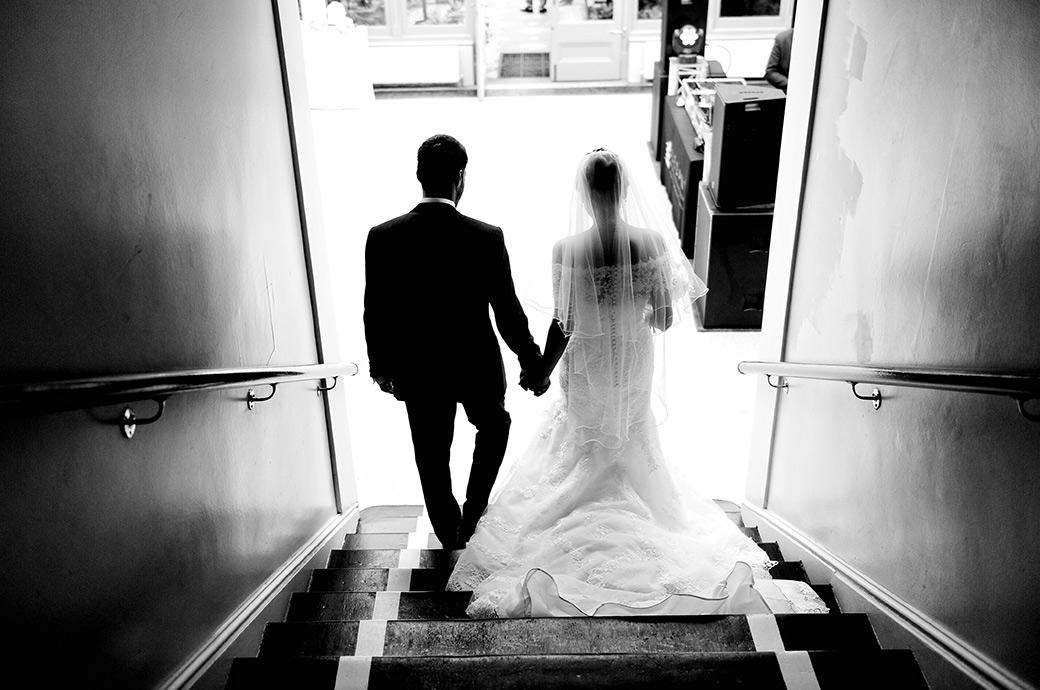 Couple hand in hand silhouetted as they walk down some stairs for their wedding reception captured at the magnificent Surrey wedding venue Hampton Court House