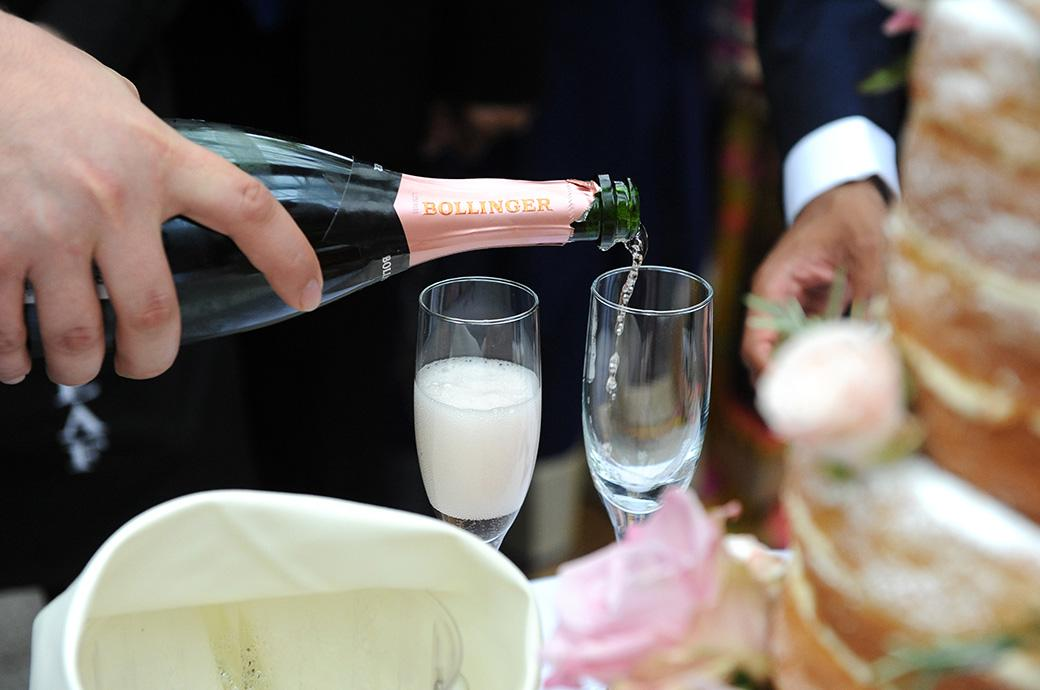 A wedding photograph of the pouring of the Bride and Groom's champagne captured at Hampton Court House in Surrey in the Conservatory