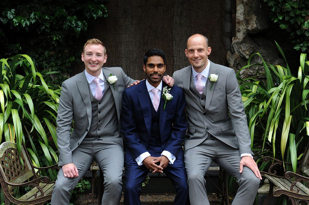 Relaxed and smiling Best men sitting with a rather nervous looking  Groom captured at Surrey venue Hampton Court House in the informal Winter Garden