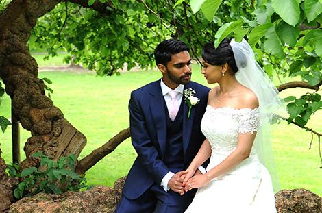 Romantic newlyweds at the wonderful Surrey wedding venue Hampton Court House hold hands and look into each others eyes as they sit on a tree trunk