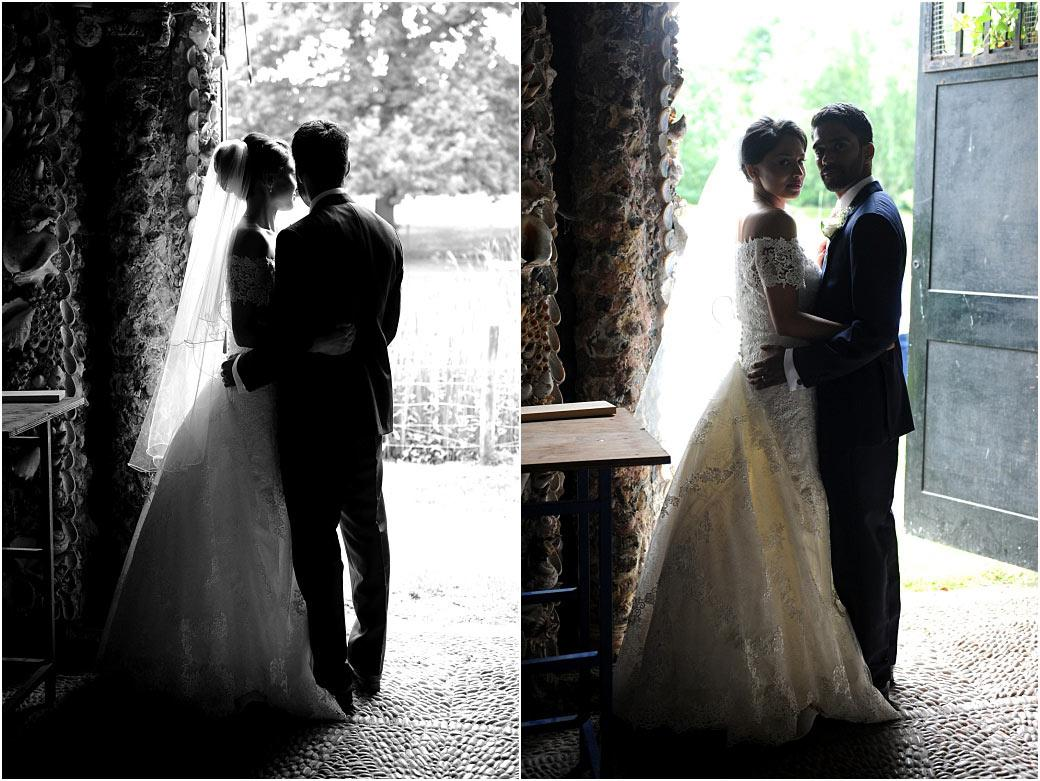 Romantic moments captured in these newlywed portraits taken at Surrey wedding venue Hampton Court House in the mysterious Shell Grotto as they stand in the doorway