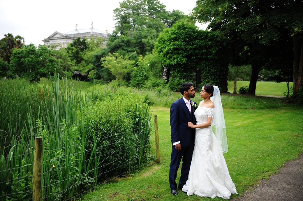 Loving looks captured in this wedding picture taken at Surrey venue Hampton Court House of the Bride and groom as they stand on the lawn by the heart shaped lake