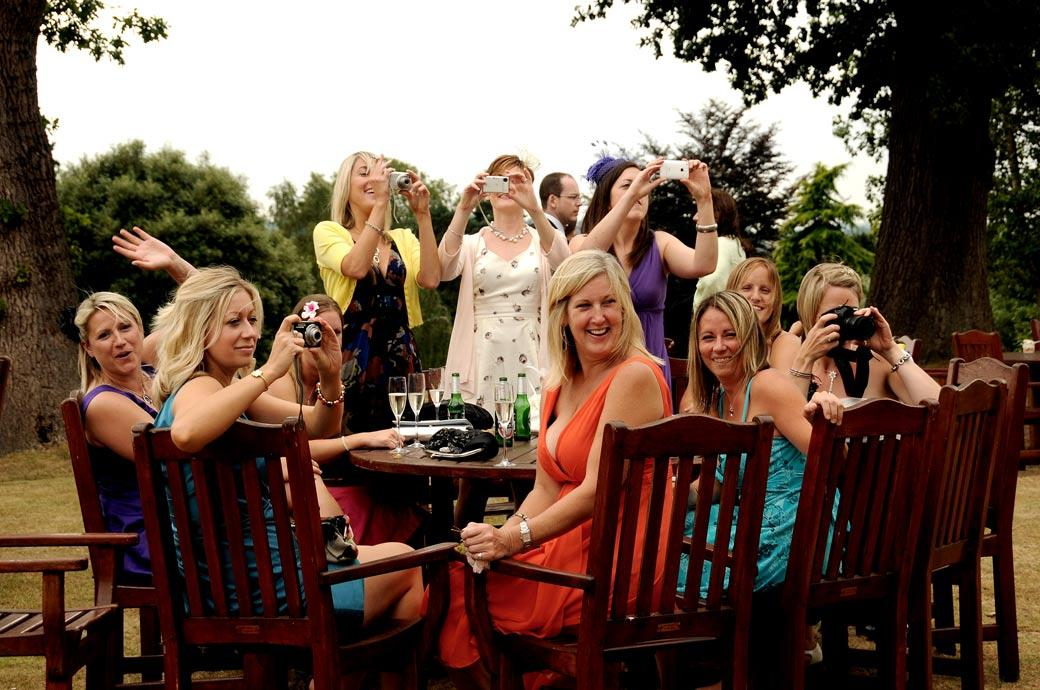 A great fun action wedding photo of the ladies ready with their cameras to get that perfect shot taken at Hartsfield Manor by Surrey Lane wedding photography