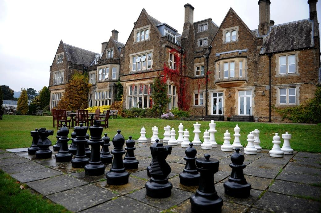 Giant garden chess board set up in the grounds of the lovely ivy clad Surrey wedding venue Hartsfield Manor set in beautiful countryside in Betchworth on a wet winter wedding day