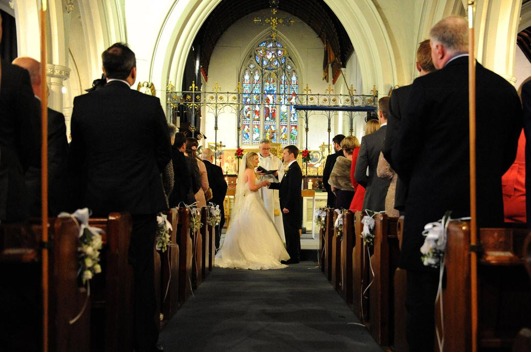 A wedding picture taken down the aisle of the church as the Bride says her marriage vows to be followed by a reception at Surrey wedding venue Hartsfield Manor, Betchworth